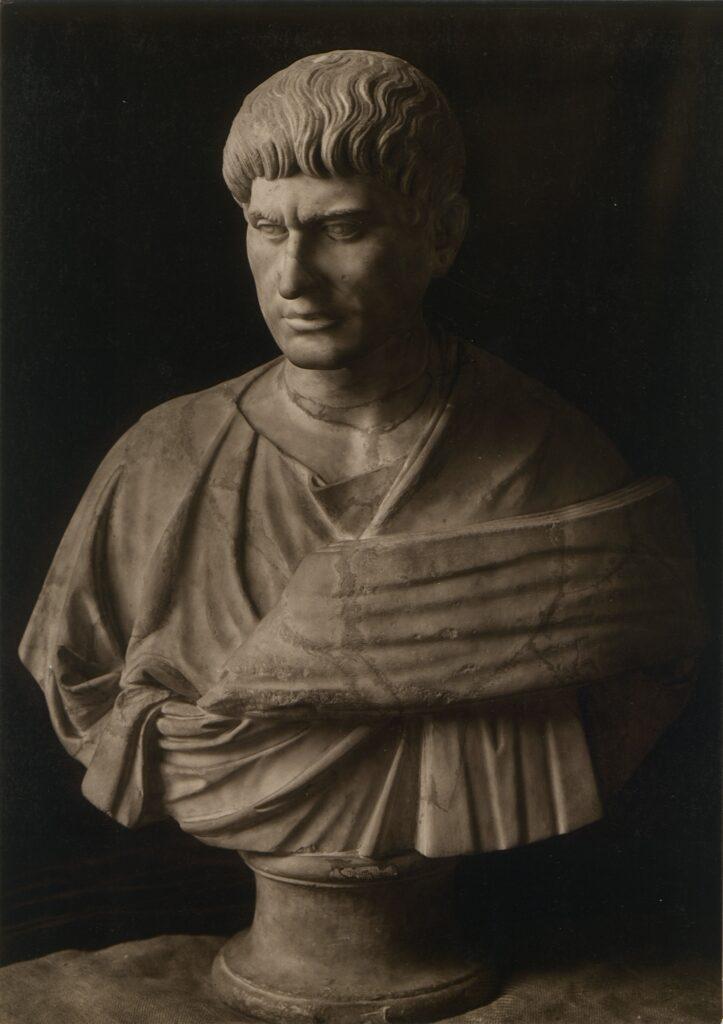 Zdjęcie przedstawia kamienne popiersie mężczyzny o gładko zaczesanych na czoło włosach i z udrapowaną na ramionach szatą. Mężczyzna, o zmarszczonych brwiach, ma gładko ogoloną twarz. Głowę kieruje lekko w dół, w lewą stronę.