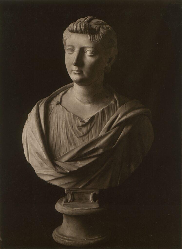 Zdjęcie przedstawia kamienne popiersie kobiety z udrapowaną na ramionach szatą. Głowę ma skierowaną lekko w lewo. Uczesanie jest typowe dla dobrze urodzonej damy czasów rzymskich.