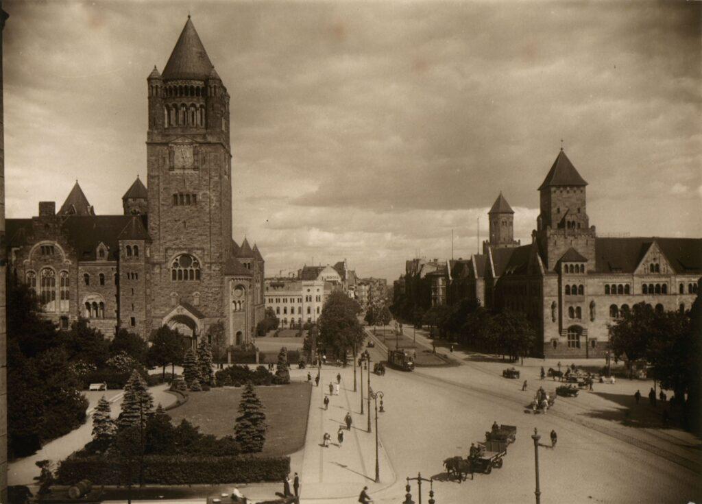 Zdjęcie przedstawia widok na Zamek i ulicę Piłsudskiego (obecnie ul. Św. Marcin). Fotografia została wykonana z balkonu dzisiejszej Auli Uniwersyteckiej.