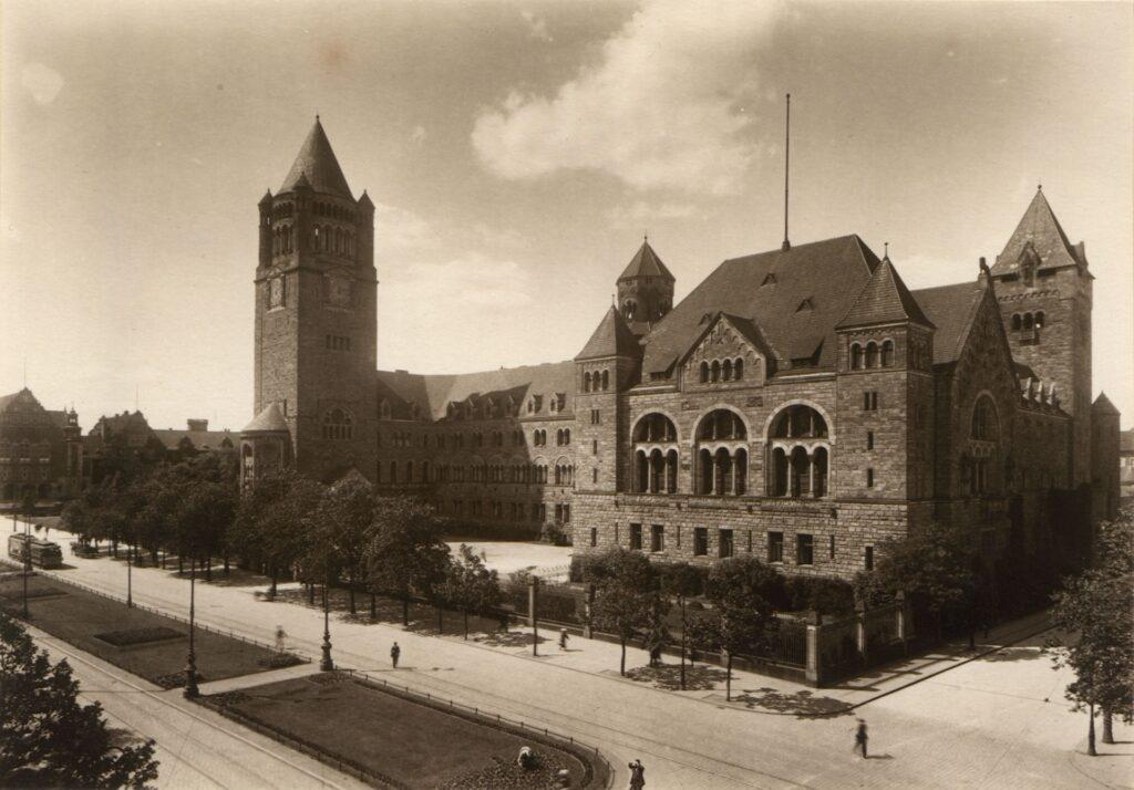 Zdjęcie przedstawia Zamek Cesarski widziany od strony południowej.  Zdjęcie wykonane w 1929 roku pokazuje pierwotny kształt budynku. Na zdjęciu dostrzec można wiele różnic w stosunku do znanej nam dziś bryły. Układ wejść do Zamku zmienił się podczas drugowojennej przebudowy. W wysuniętej części reprezentacyjnej, mieszczącej pierwotnie Salę Tronową, wejście znajdowało się z boku, od strony dzisiejszej ulicy Kościuszki. Uwagę zwraca wysoki na pięć metrów parkan, podkreślający odosobnienie i wysoką rangę cesarskiej rodziny.