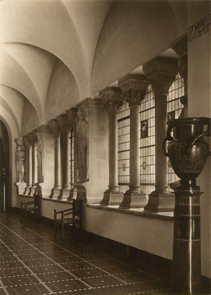 Perspektywiczne ujęcie wnętrza przedstawia historyzujące kolumny w otworach okiennych z barwnymi wstawkami z witrażowymi przedstawieniami znaków zodiaku, fragment romanizującego sklepienia, stylizowane krzesła oraz wazę na postumencie.