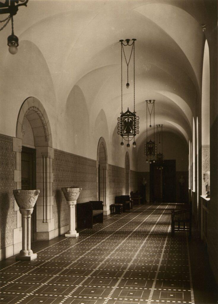 Zdjęcie przedstawia widok korytarza pierwotnie prowadzącego do pokojów cesarzowej Augusty Wiktorii. Perspektywiczne ujęcie wnętrza pozwala dostrzec stylizowane elementy, takie jak ławy, krzesła, kwietniki wzorowane na średniowieczne chrzcielnice, a także dekoracyjne lampy.