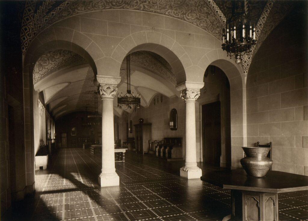 Głównym elementem zdjęcia są dwie, jasno oświetlone, pseudoromańskie kolumny o rzeźbionych kapitelach. W pomieszczeniu znajdują się historyzujące meble, żyrandole stylizowane na średniowieczne oraz geometryzująca posadzka.
