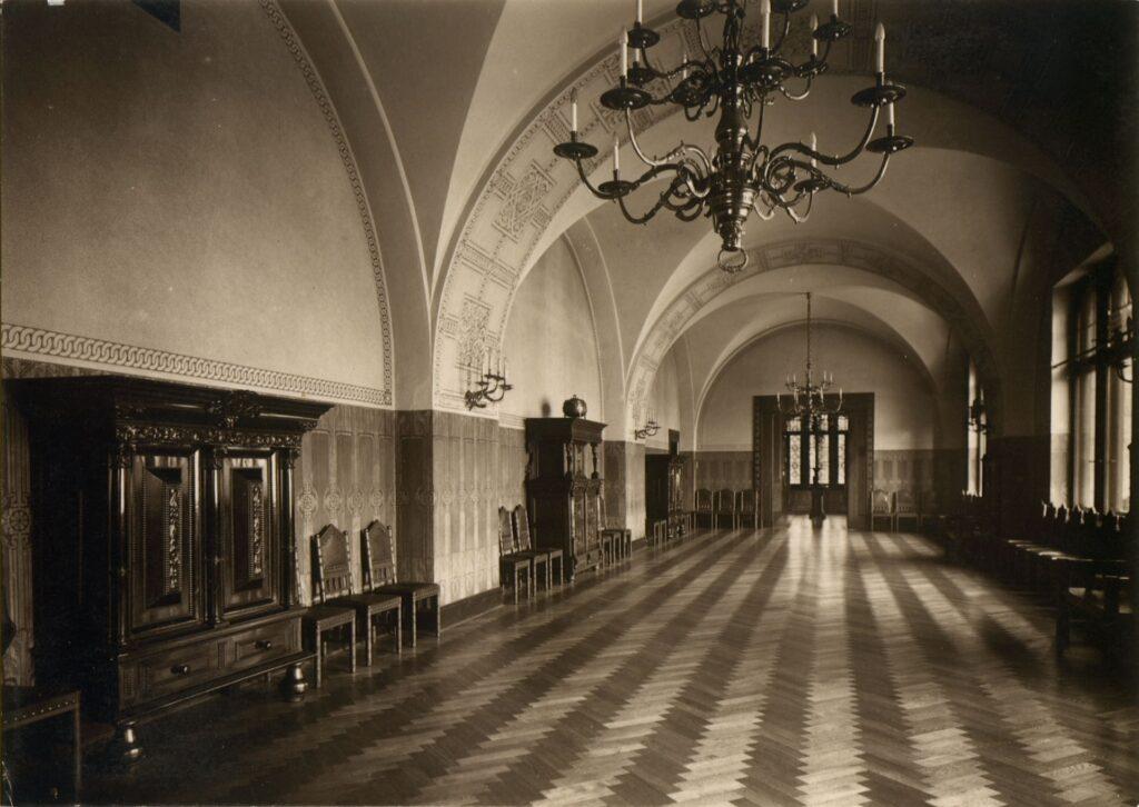Jasno oświetlone pomieszczenie wyposażone jest w stylizowane meble i oświetlenie, parkiet jest drewniany. W górnej części fotografii uwagę zwraca żyrandol, wzorowany na żyrandolu z katedry w szwedzkim mieście Visby.