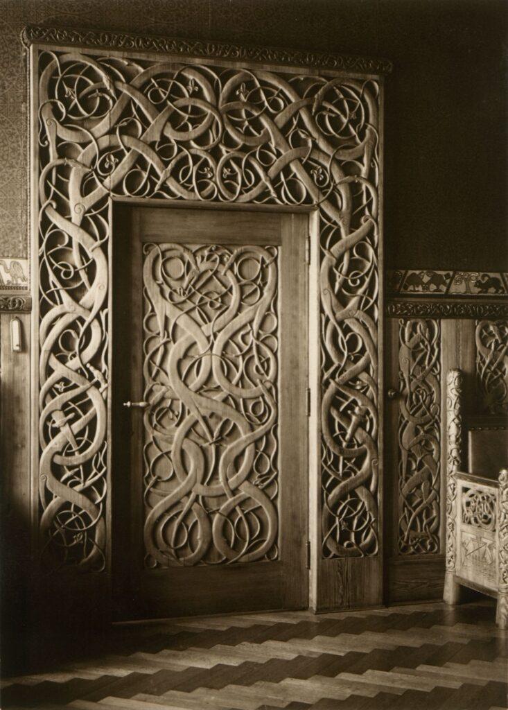 Na zdjęciu dostrzec można elementy stylizowane na staroskandynawskie. Większą część zdjęcia zajmują drzwi i portal z ornamentem plecionkowym. Podziwiać można starannie wykonaną dekorację ornamentalną drzwi jednoznacznie odwołującą się do średniowiecznych wzorców drewnianej architektury kościelnej Norwegii.