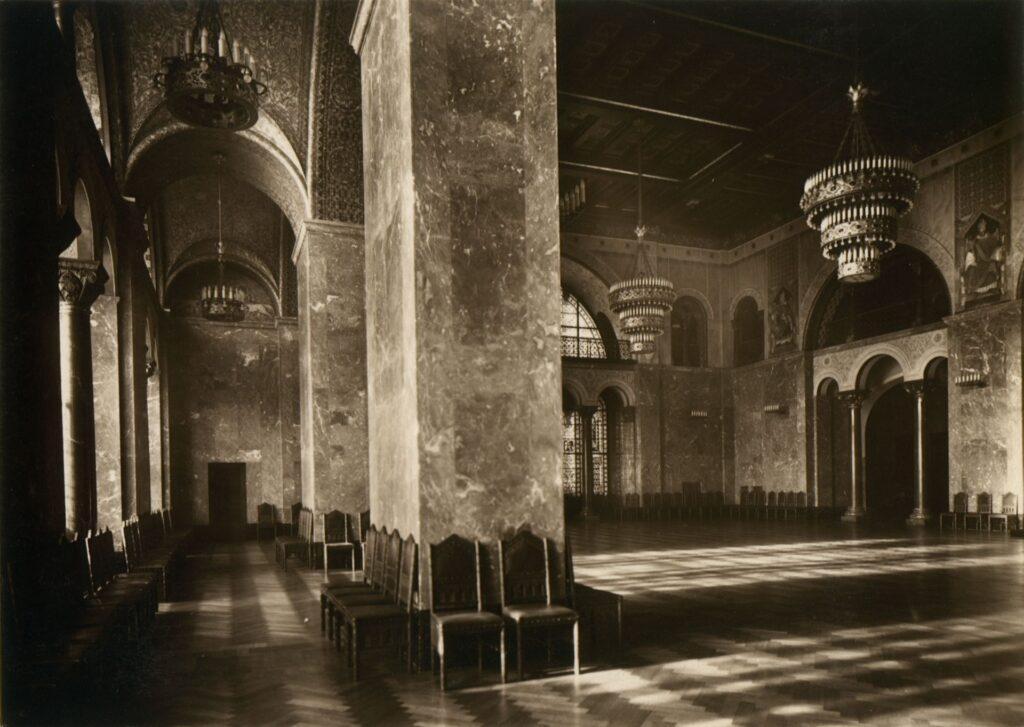 Zdjęcie w sepii przedstawia widok ogólny Sali Tronowej.  Na pierwszym planie fotografii dominującym elementem jest masywny filar obłożony żyłkowanym marmurem. Wokół niego ustawiono krzesła z charakterystycznymi arkadkowymi szczytami