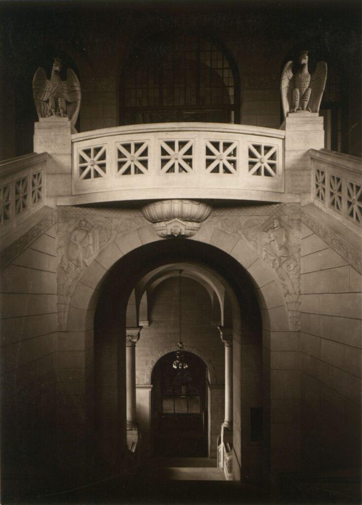 Ciekawe ujęcie przedstawia balustradę pierwszego piętra oświetloną mocnym, sztucznym światłem, podczas gdy dolna, parterowa część, częściowo niknie w mroku. Z łagodnego półmroku wyłania się delikatny rysunek płaskorzeźbionych dekoracji pod balustradą.