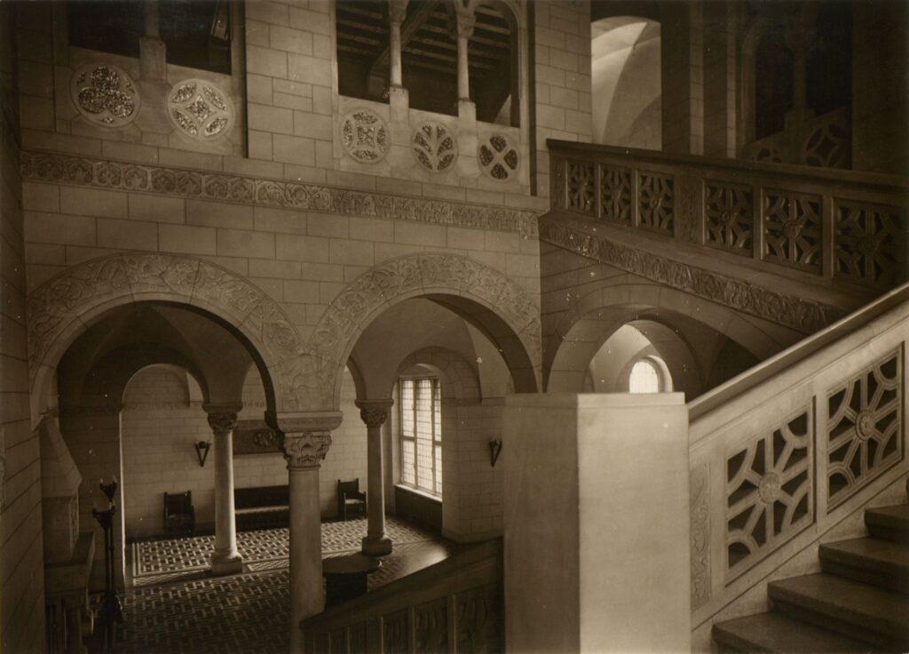Zdjęcie przedstawia schody cesarskie w zachodnim skrzydle Zamku. W dolnej części zdjęcia widać oświetlony przedsionek, do którego udawano się z przejazdu bramnego. Fotografia, utrzymana w jasnych barwach, podkreśla przede wszystkim jasny odcień i fakturę piaskowca użytego do wykończenia przestrzeni schodów.  Liczne arkady otwierają perspektywę na kolejne plany pomieszczenia.