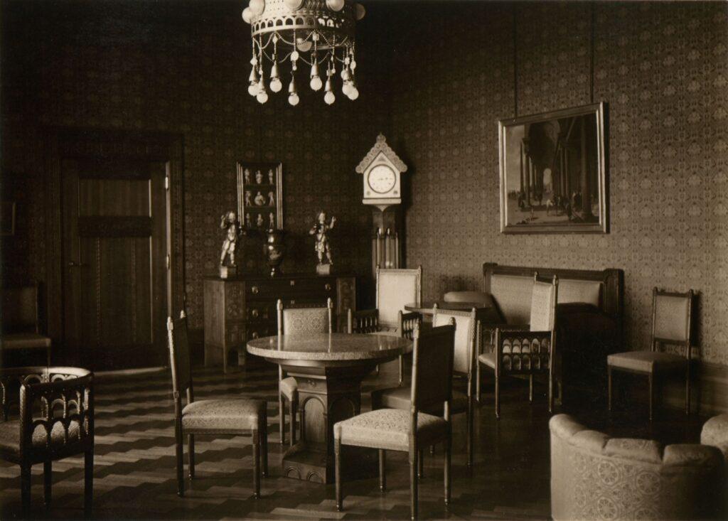 Zdjęcie przedstawia pokój dzienny cesarzowej Augusty Wiktorii. Uwagę zwracają liczne krzesła, zajmujące większość część pomieszczenia, tworzące skupiska wokół niewielkich stolików. Pod ścianami ustawiono ławę i komodę z wazą i dekoracyjnymi figurami. W rogu pokoju znajduje się jasno oświetlony zegar z trójkątnym naczółkiem.  U góry widać bogato zdobiony, kolisty żyrandol ze zwisającymi żarówkami, których oprawy mają naśladować wisiory ze szlachetnych kamieni.