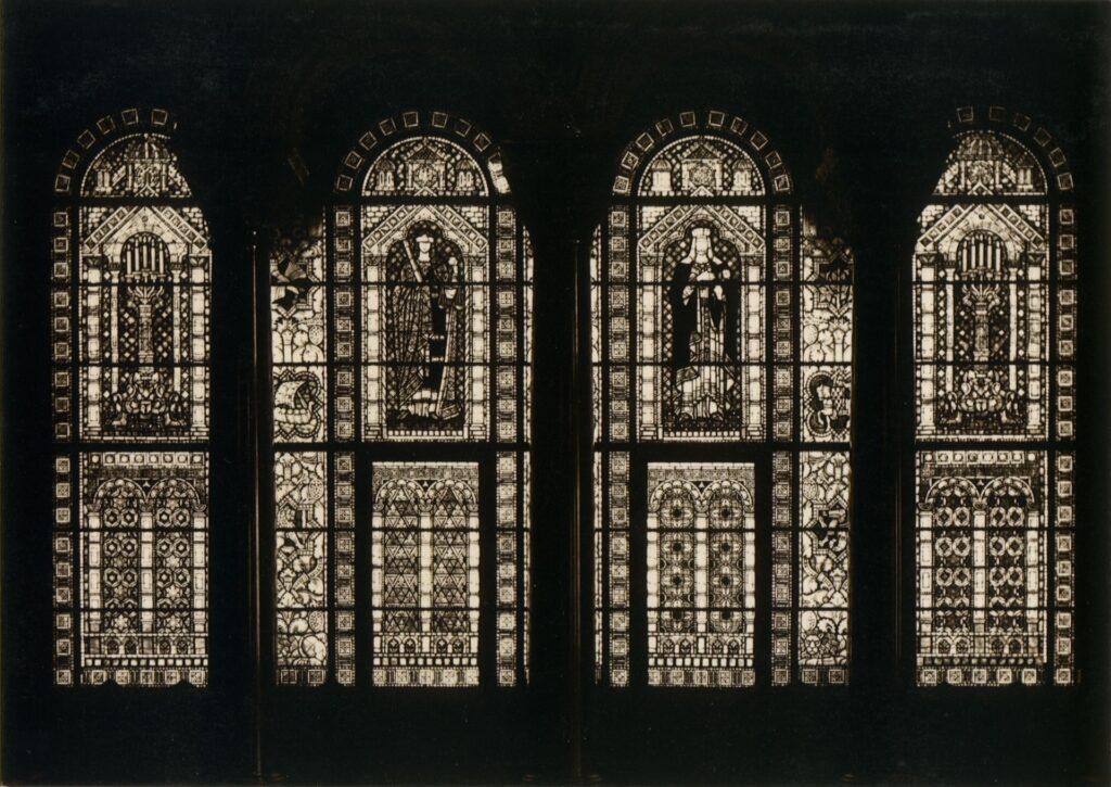 Zdjęcie przedstawia witraże w Sali Tronowej. Fotografia operuje kontrastem pomiędzy ciemnymi kolumnami i ścianami, a jasnymi, wyraźnymi przestawieniami witrażowymi. Widoczny jest tylko zarys trzech kolumn, detale takie jak rzeźbione dekoracje kapiteli, giną w mroku. Natomiast cztery części witraża, rozdzielonych kolumnami, pozwalają na przyjrzenie się szczegółom przedstawień.   Witraże operują dekoracjami, zarówno geometryzującymi, jak i figuratywnymi.  W dolnej partii widać motywy architektoniczne (kolumny, łuki) wypełnione ornamentami geometrycznymi i roślinnymi. W górnej części witraży uwagę zwracają przedstawienia alegoryczne, takie jak uosobienie sprawiedliwości z wagą i mieczem.