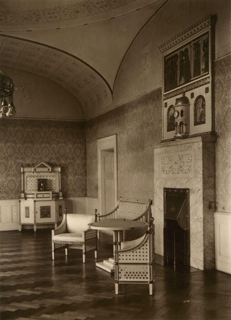 Zdjęcie przedstawia pokój przyjęć cesarzowej. Widoczne są jasne meble i inne elementy wyposażenia składające się na luksusowe i eleganckie wnętrze. Po prawej stronie widać biały, marmurowy kominek, a nad nim malarskie przestawienie sceny Nawiedzenia.
