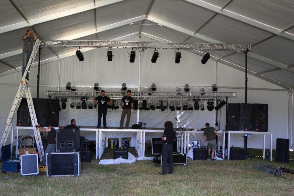 Ekipa techniczna CK ZAMEK podczas montażu sceny w namiocie festiwalowym. Zdjęcie przedstawia siedmiu mężczyzn przeprowadzających prace montażowe na scenie wewnątrz wielkiego, białego namiotu o stalowej konstrukcji. Na scenie, wokół niej i pod nią porozstawiane są liczne elementy techniczne, oświetleniowe i nagłośnieniowe.