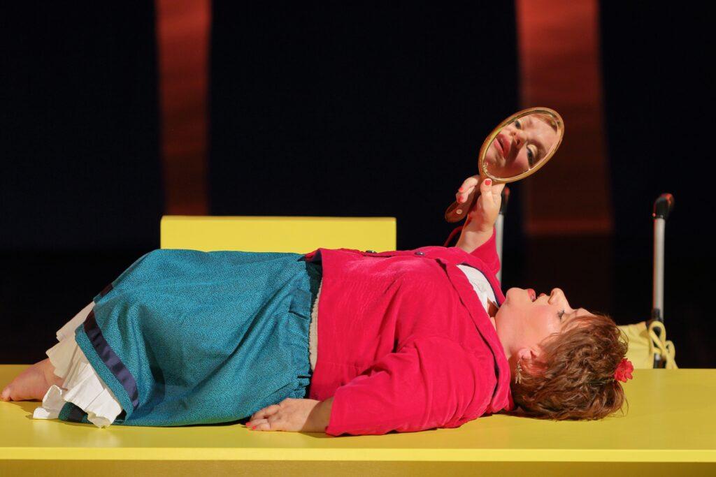 Kadr bliski ukazuje kobietę leżącą na wznak na żółtej płaszczyźnie, prawdopodobnie jest to blat stołu. Aktorka jest osobą niskorosłą. Ma na sobie intensywnie różowy żakiet i jasnoniebieską, sięgającą bosych stóp spódnicę z białą falbaną u dołu. Kasztanowe, krótkie włosy ozdabia czerwony kwiat. W wyciągniętej ku górze prawej ręce artystka trzyma owalne lusterko. Odbija się w nim jej twarz widziana en face. Miękkie rysy, błękitne oczy, pełne, rozchylone usta. Twarz w odbiciu zdaje się spoglądać w oko obiektywu. W tle majaczą niewyraźne kształty scenografii.