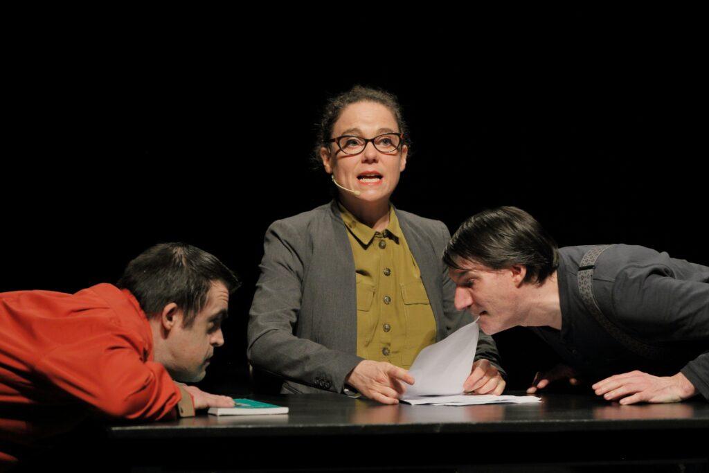 Bliski kadr ukazuje troje aktorów skupionych wokół czarnego blatu stołu. Na wprost siedzi kobieta w oliwkowej koszuli i szarej marynarce. Ma ciemne, upięte z tyłu włosy, a na nosie okulary. W dłoniach trzyma kartkę papieru. Przed nią leżą też inne dokumenty. Jej postawa i wygląd przywodzą na myśl surową nauczycielkę lub urzędniczkę. Po obu stronach artystki znajdują się nachyleni nad blatem stołu mężczyźni. Ten po prawej, w szarej bluzce, chwyta ustami kartkę papieru trzymaną przez kobietę. Aktor z lewej natomiast, ubrany w czerwoną koszulę przypatruje się temu z uwagą, opierając dłonie i brodę na leżącej na blacie książce.
