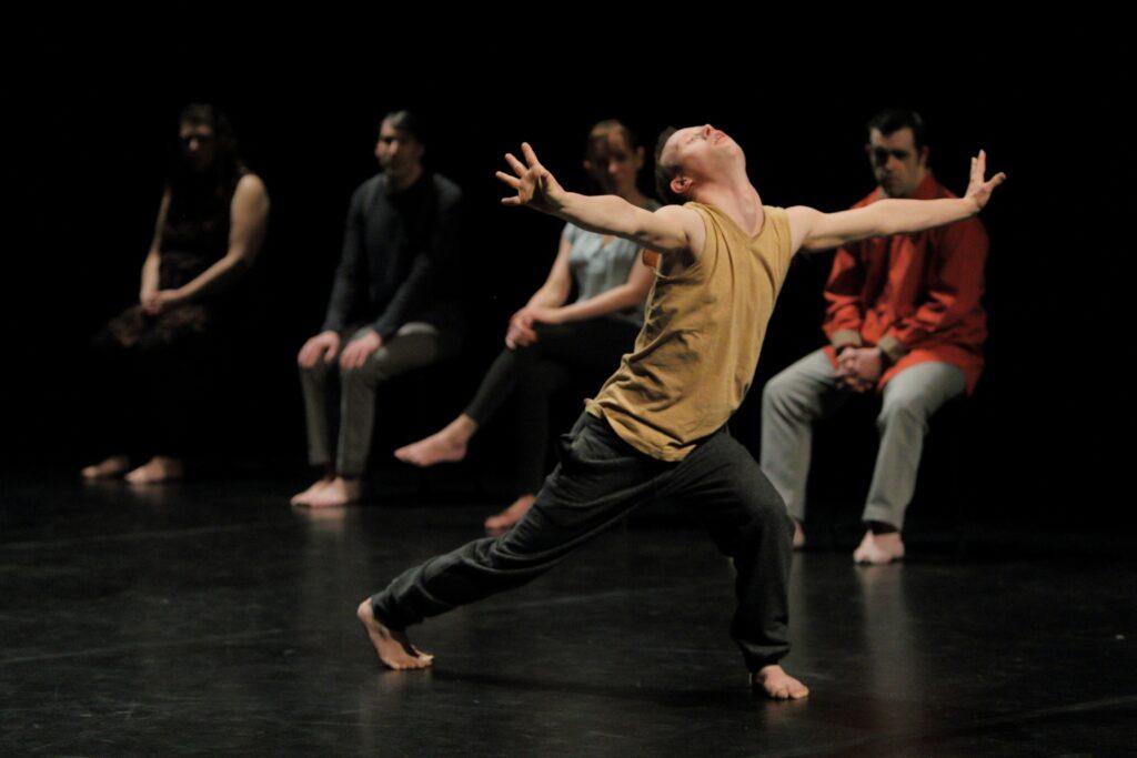 Pięcioro aktorów i aktorek znajduje się na pustej, czarnej scenie. Mają wygodne, niewyróżniające się niczym szczególnym stroje oraz bose stopy. Na pierwszym planie jeden z tancerzy ekspresyjnie prezentuje pozę taneczną: długi wykrok do przodu, głowa uniesiona, ręce rozrzucone na boki. Pozostałe cztery postacie – dwie kobiety i dwóch mężczyzn – znajdują się na drugim, nieostrym planie. Siedzą wyprostowani na niewidocznych dla obserwatora krzesłach. Za nimi jest już tylko nieprzenikniona czerń.