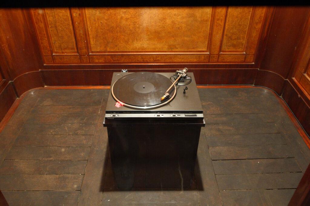 W zabytkowej, drewnianej, zamkowej nieczynnej windzie artysta umieścił stary gramofon z płytą.