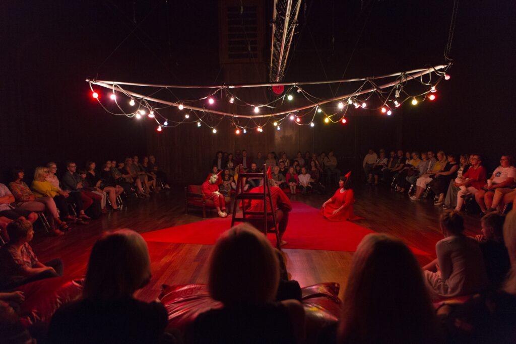 Plan ogólny przedstawia kwadratową przestrzeń zaaranżowanej na podłodze sceny oraz siedzącą wokół na krzesłach i poduchach widownię. Pośrodku sceny leży duży trójkąt wycięty z czerwonej wykładziny. Na jego bokach siedzą trzy osoby. Kobieta po prawej – na podłodze, mężczyzna po lewej – na niskim fotelu, a trzeci z aktorów przycupnął tyłem do obiektywu na małej drabince. Artyści ubrani są na czerwono, na głowach mają małe spiczaste czapeczki w tym samym kolorze. Nad ich głowami wisi trójkątna konstrukcja opleciona sznurem wielobarwnych lampek.