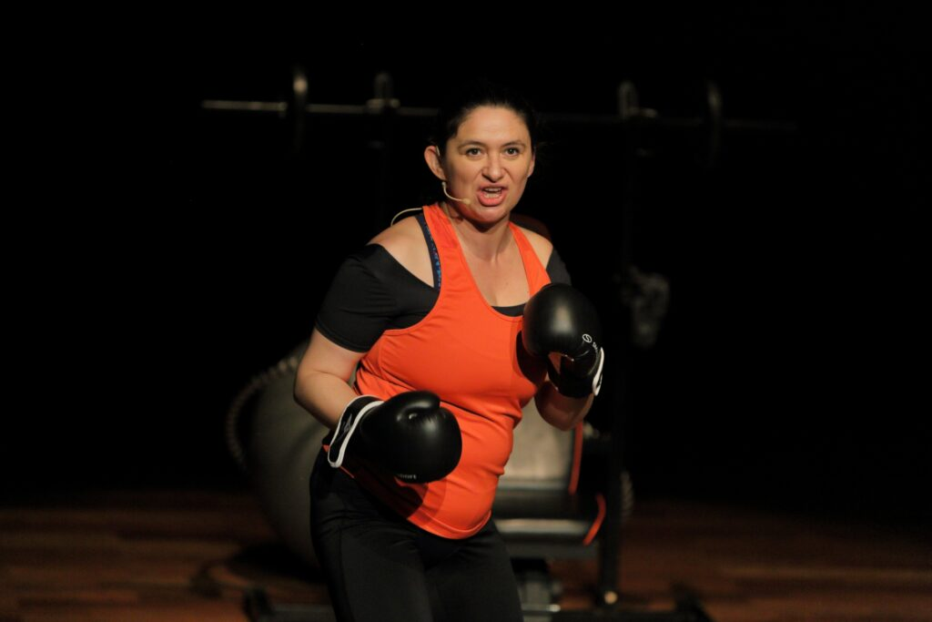 Portret kobiety w sportowym, czarno-czerwonym stroju z bokserskimi rękawicami na rękach. Aktorka zdaje się szykować do oddania ciosu. Jest pełna energii i determinacji, może nawet wściekłości. W tle, z mroków sceny wyłaniają się niewyraźne kontury przyrządów do ćwiczeń – ławeczki, sztangi, hantli.