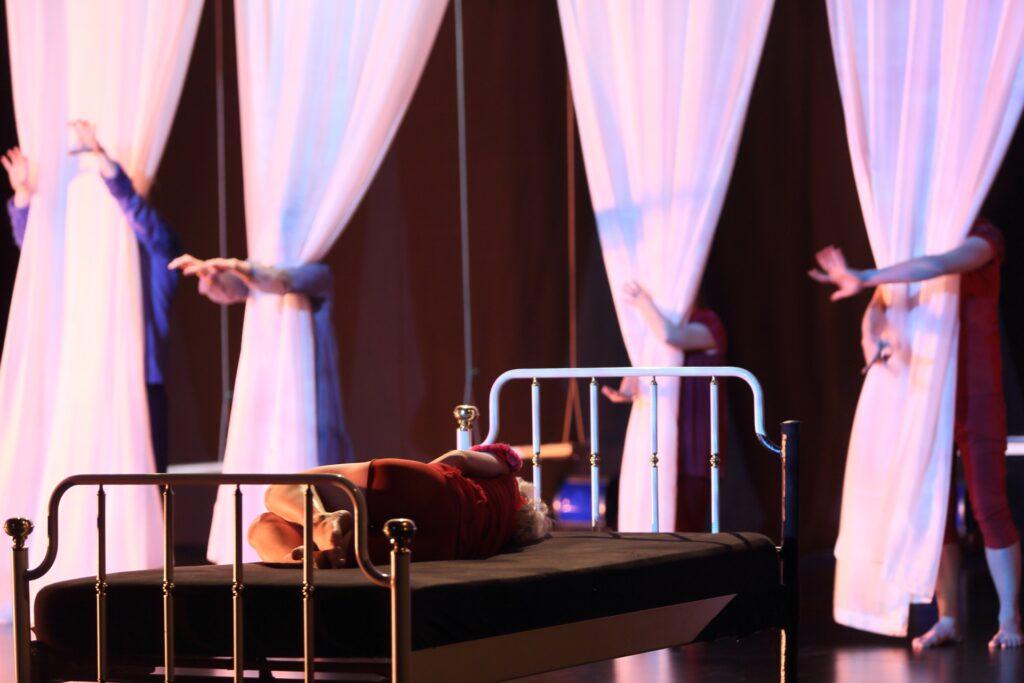 Na pierwszym planie znajduje się stylowe, białe metalowe łóżko z wysokimi zagłówkami. Na czarnym materacu leży odwrócona tyłem kobieta. Ubrana jest w czerwone krótkie spodenki i bluzkę w tym samym kolorze. Ma bose stopy i podkurczone nogi. Dalszy plan jest nieostry. W głębi ciemnej sceny wiszą cztery pasy białej tkaniny. Za każdą z nich majaczy postać ludzka. Aktorzy ukryci za kotarami są właściwie niewidoczni dla widza. Najważniejszym elementem na fotografii są ich ręce – wyłaniają się zza tkaniny, obejmują ją.