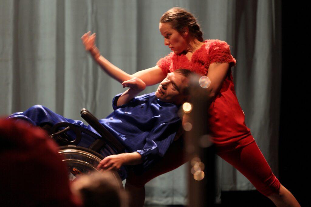 Zbliżenie na dwoje tancerzy uchwyconych w ruchu. Ona – szatynka z długimi, zaplecionymi w warkocz włosami, o delikatnych rysach twarzy. Ma na sobie czerwoną bluzkę i legginsy w tym samym kolorze. Stawia długi krok, unosząc prawą dłoń. On – szczupły, krótkowłosy mężczyzna, ubrany w niebieski, połyskliwy kostium przypominający piżamę. Siedzi na wózku. W tanecznej pozie odchylony jest do tyłu, opierając się o swą partnerkę. Za aktorami majaczy nieostra biała kotara.