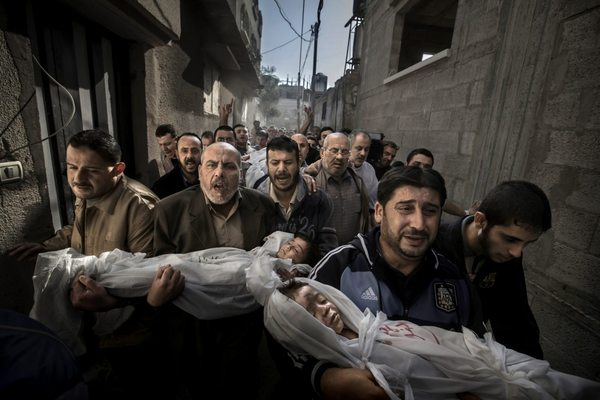 Fotografia przedstawia pochód mężczyzn niosących ciała dwojga zmarłych, małych dzieci, zabitych podczas izraelskiego nalotu na Strefę Gazy w listopadzie 2012 roku. Dziewczynka i chłopiec owinięci są folią. Na wszystkich twarzach mężczyzn widać ogromną rozpacz i smutek. Tłem pracy są ruiny betonowych domów.