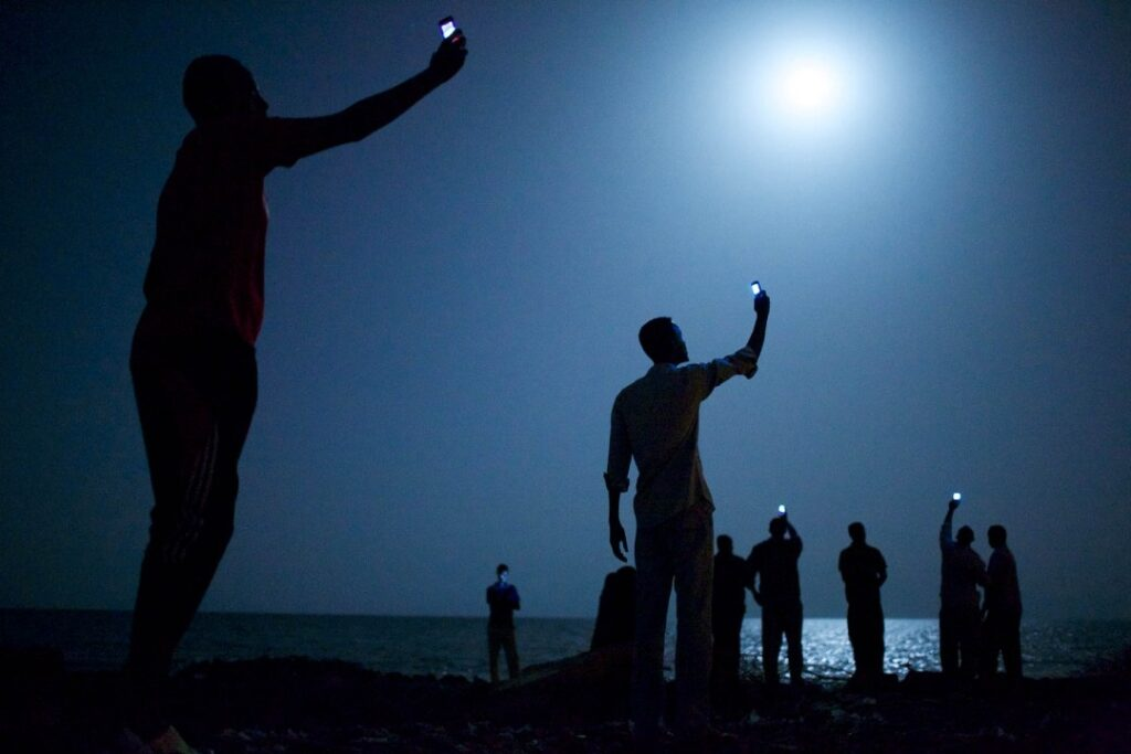 Na fotografii widać stojącą na plaży grupę ludzi, trzymających w uniesionych dłoniach telefony komórkowe. Mężczyźni próbują złapać sygnał sieci komórkowej. Zdjęcie zostało wykonane nocą, przy blasku księżyca w pełni, dzięki czemu niebo i spokojne, bez fal, morze są rozświetlone. Dodatkowym źródłem światła jest kilka ekranów telefonów.