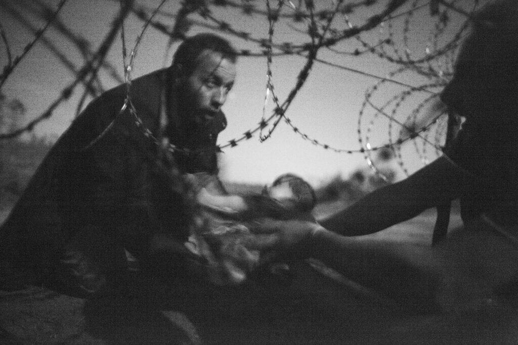 Na czarno-białym zdjęciu, wykonanym w nocy, widać mężczyznę podającego pod zaporą, wykonaną z drutu kolczastego, małe dziecko stojącej po drugiej stronie kobiecie. Rodzina próbuje przejść przez stojące na granicy dwóch państw zasieki. Zdjęcie jest niewyraźne, bowiem fotograf nie mógł wykorzystać lampy błyskowej, aby nie zdradzić czasu i miejsca ucieczki imigrantów.