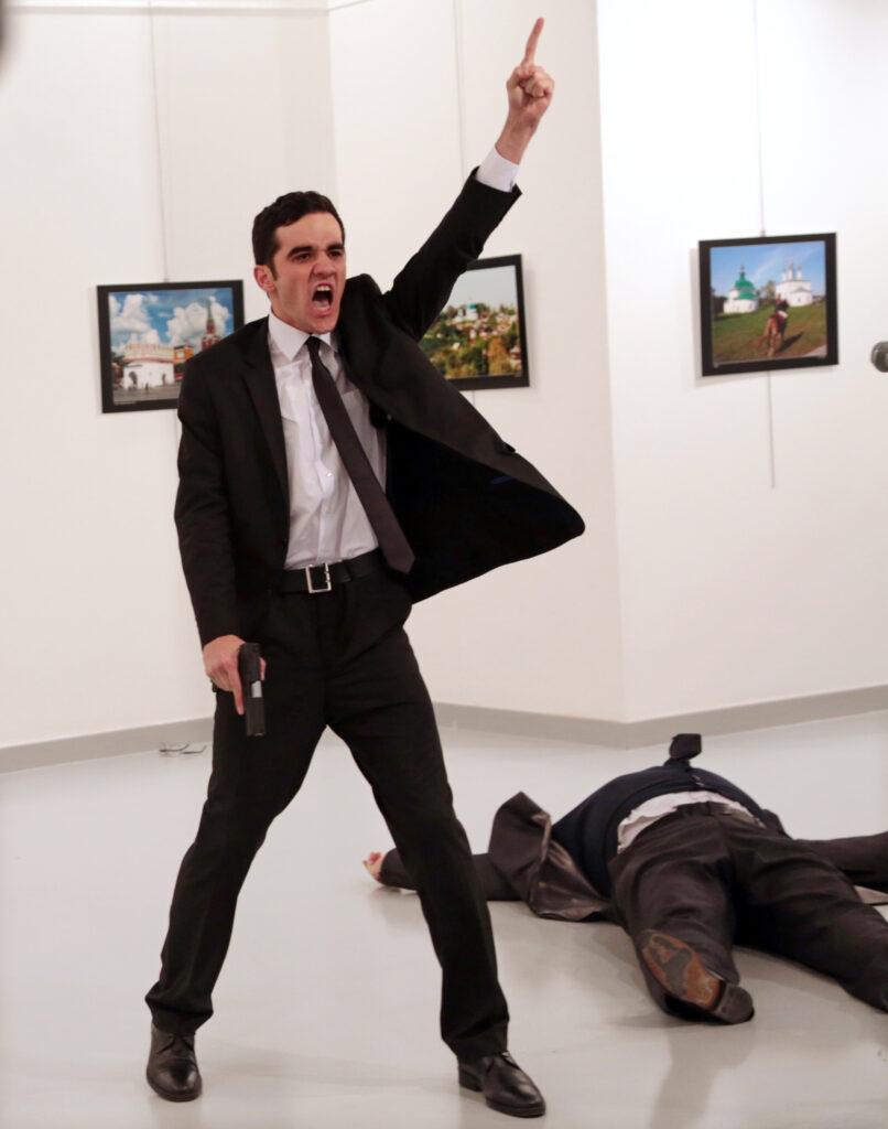 Na zdjęciu został uchwycony moment zabójstwa rosyjskiego ambasadora w Ankarze. Na pierwszym planie widzimy ubranego w garnitur, białą koszulę i krawat młodego mężczyznę, który w jednej ręce trzyma pistolet, drugą ma uniesioną do góry. Usta ma otwarte, jakby  w krzyku. Obok niego, po prawej stronie leży ciało drugiego mężczyzny, również ubranego w garnitur. Na białych ścianach w tle zawieszone są trzy kolorowe fotografie w ramach. Podłoga pomieszczenia jest jasnoszara, błyszcząca.