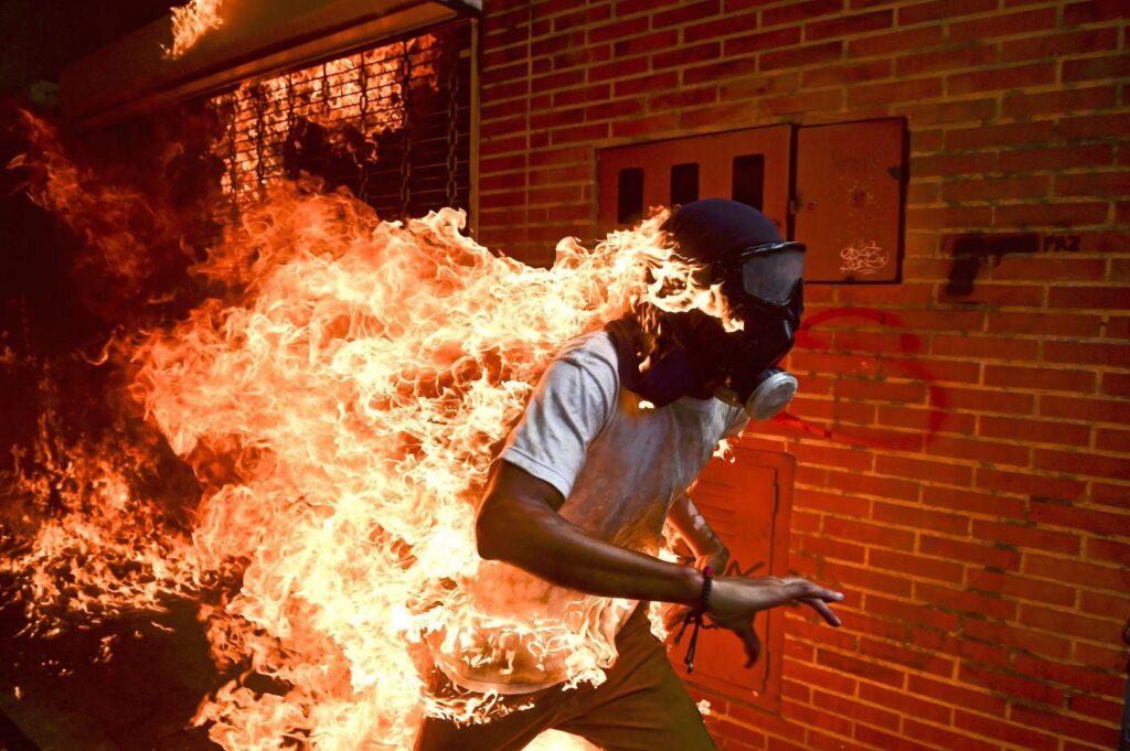 """Fotografia przedstawia młodego, biegnącego mężczyznę, który ma na głowie maskę gazową. Jego całe ciało płonie, a buchający ogień tworzy ogromne smugi. Tłem zdjęcia jest ceglany, rozgrzany od temperatury mur z małym graffiti. To pistolet z napisem """"paz"""" oznaczającym pokój."""