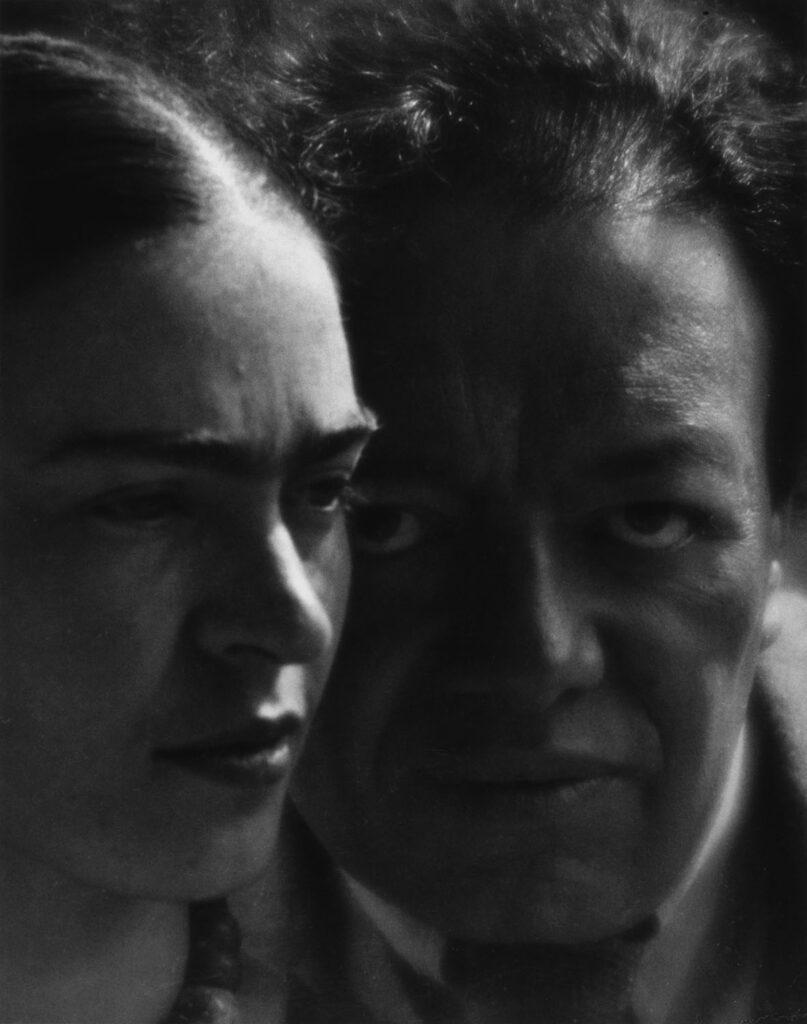 Czarno-biała fotografia przedstawia Fridę Kahlo i Diego Riverę. Frida znajduje się po lewej stronie i patrzy w dal, natomiast wzrok Diego skierowany jest prosto w obiektyw fotografa.