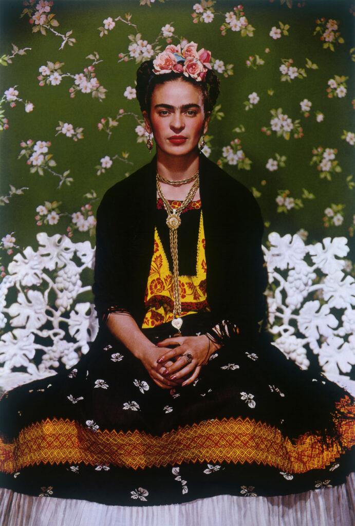Na kolorowej fotografii widać siedzącą na białej, ażurowej ławce Fridę ubraną w czarną suknię, zdobioną żółto-pomarańczowymi wzorami. Na głowie Fridy znajduje się misternie upięty warkocz z wplecionymi różami, na szyi zaś widzimy długi, złoty naszyjnik. Tło obrazu jest zielone z drobnymi, białymi kwiatkami.