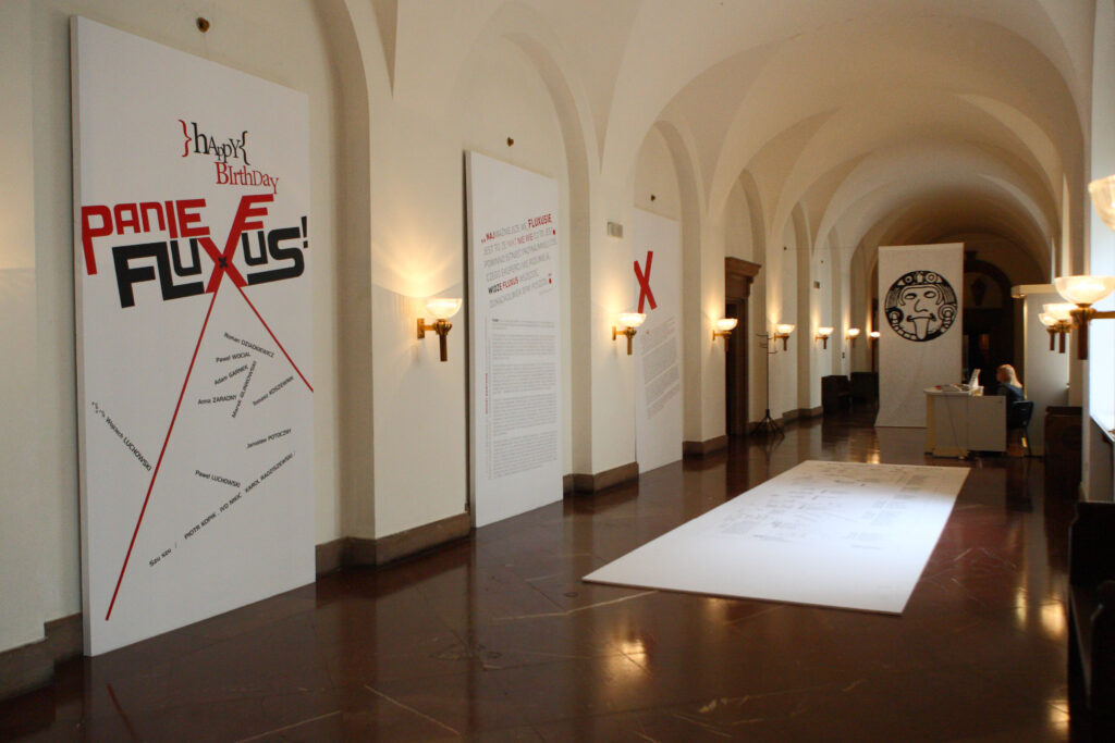 Fotografia przedstawia zamkowy duży korytarz z półkolistym sklepieniem, na ścianach którego półkoliste arkady wyznaczają równy rytm. Hol jest biały, poza podłogą wykonaną z czerwonego marmuru. We wnękach arkad znajduje się tablica z tytułem wystawy, nazwiskami artystów oraz tekstami wprowadzającymi w jej tematykę. Pośrodku holu, na podłodze leży dużych rozmiarów panel przypominający wielką kartkę, na którym w graficzny sposób, na wzór mapy z ulicami, przedstawiony został rozwój gatunków sztuki od starożytności do lat 60. XX wieku. W połowie korytarza powieszona jest biała tkanina z czarnym graficznym znakiem przedstawiającym twarz z wyciągniętym językiem − symbol ruchu Fluxus.