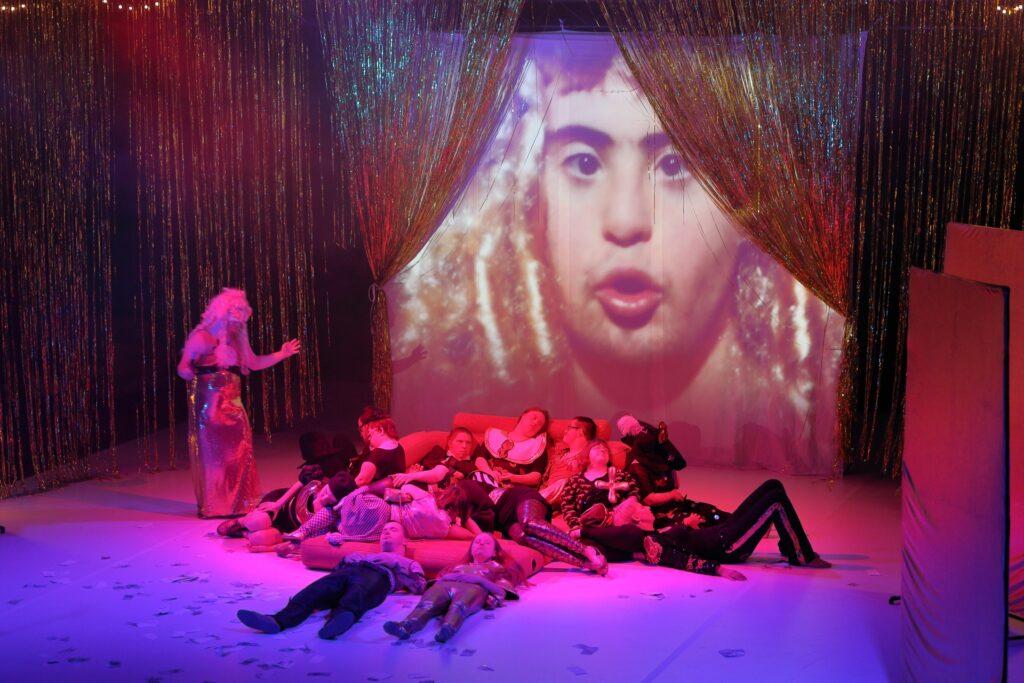 Zdjęcie ukazuje grupę kilkunastu aktorek i aktorów leżących na dużym dmuchanym materacu ustawionym pośrodku pustej, białej podłogi. Każde z nich przybrało inną pozycję, razem tworzą kłębowisko ciał. Nieco z boku, po lewej stronie stoi samotna postać przypatrująca się leżącym. To prawdopodobnie mężczyzna w złotej, połyskliwej sukni i blond peruce. Na tyłach sceny rozpięto białą tkaninę, na której wyświetlana jest projekcja. Uchwycony na fotografii kadr filmowy przedstawia portret młodego mężczyzny z zespołem Downa. Jego twarz okalają pukle platynowych włosów. Wokół ekranu, od sufitu do podłogi zwieszają się niczym kotara delikatne, złote paski.