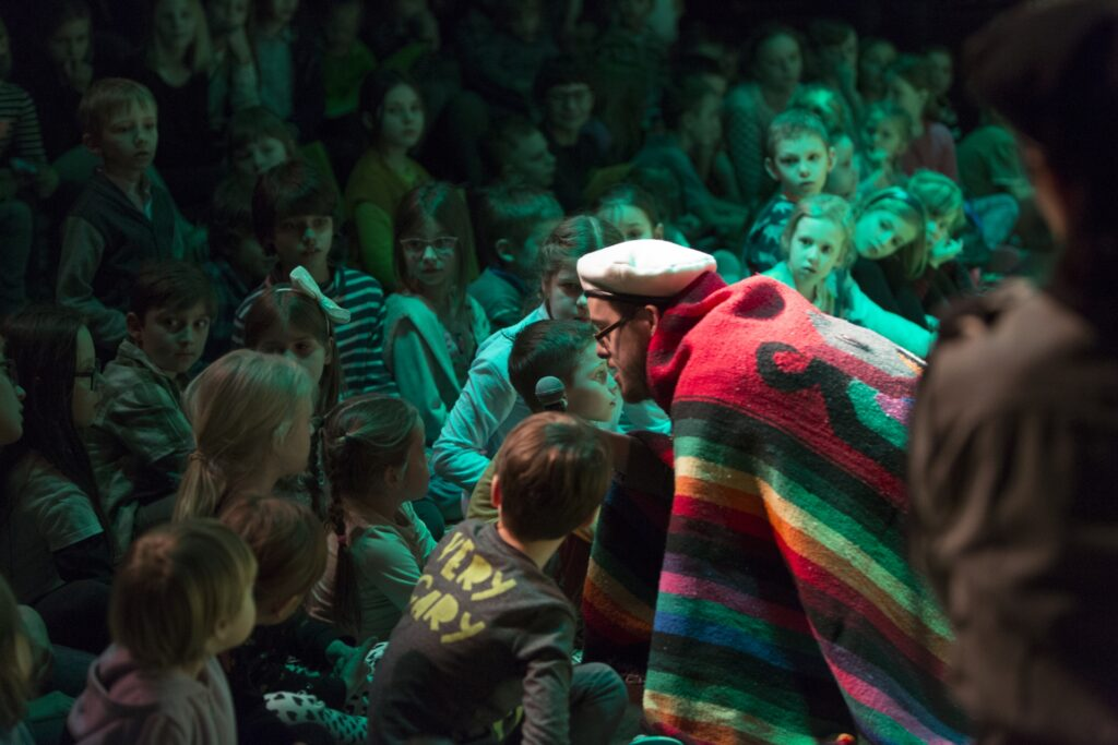Zdjęcie przedstawia aktora pochylającego się nad dziećmi siedzącymi na podłodze w pierwszych rzędach widowni. Mężczyzna ma na głowie biały beret. W wyciągniętej ręce trzyma mikrofon. Cały okryty jest pasiastą, barwną tkaniną, która jaskrawo odcina się od zalanego seledynowym światłem otoczenia. Siedzące wokół dzieci patrzą na aktora z wielkim zainteresowaniem.