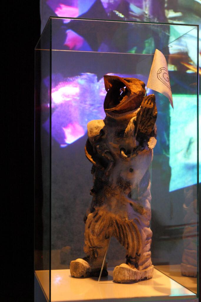 Prawie cały kadr wypełnia szklana gablota, w której znajduje się wykonana z drewna postać przypominająca człowieka z głową ryby i trzymająca chorągiewkę. Z tyłu za gablotą widzimy różnokolorowe światła.