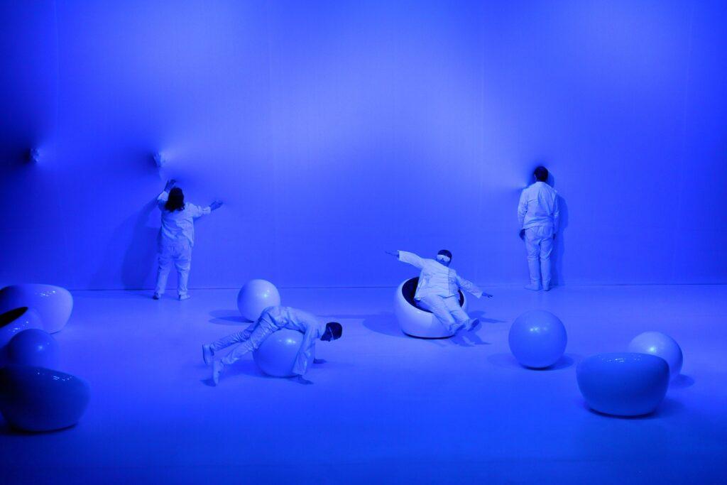 Scena uchwycona na fotografii zalana jest intensywnie niebieskim światłem. Biała podłoga, biała ściana, białe elementy scenografii, ubrani na biało aktorzy – wszystko jest niebieskie. Kadr przedstawia czworo aktorów w sterylnej, niemal pustej przestrzeni. Na podłodze, w przypadkowym ustawieniu znajduje się pięć półokrągłych siedzisk oraz cztery duże piłki. Każdy z artystów robi coś innego. Nie wchodzą ze sobą w interakcję. Postać po prawej stronie stoi tuż pod tylną ścianą tyłem, na baczność. Kolejna osoba, z wyciągniętymi nogami i uniesionymi rękami, siedzi na niskim fotelu o kolistym przekroju. Leżący obok mężczyzna balansuje na piłce. Kobieta z lewej wyciągniętymi rękoma dotyka tylnej ściany. Obok niej odciskają się dwie dłonie, co pozwala sądzić, że ściana nie jest twarda – tworzy ją napięty materiał.