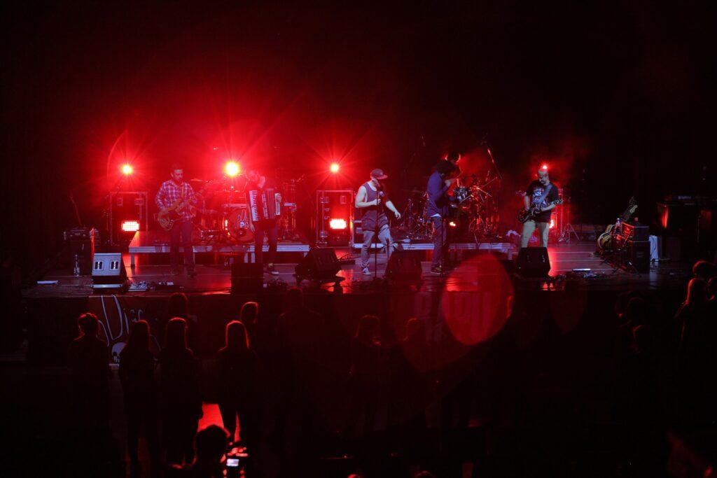 Zdjęcie zostało wykonane zza widowni. Na pierwszym planie widzimy ciemne sylwetki osób stojących przed sceną, które oświetla czerwone światło padające ze sceny. Na scenie stoi sześciu muzyków oświetlonych od tyłu intensywnym czerwonym światłem. Od lewej: gitarzysta, akordeonista, dwaj wokaliści i basista. Nieco z tyłu na podwyższeniu znajduje się perkusista.
