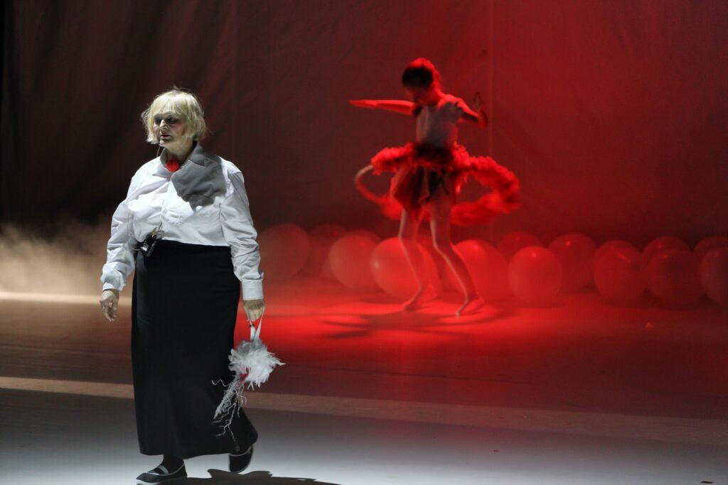 Zdjęcie przedstawia dwa plany znacząco różniące się kolorystyką. Na pierwszym z nich, po lewej stronie, stoi starsza kobieta oświetlona od góry zimnym, białym światłem. Ubrana jest w białą, męską koszulę i ciemną, długą do kostek, spódnicę. Ma średniej długości blond włosy i ręce opuszczone wzdłuż ciała. W lewej dłoni trzyma biały rekwizyt przypominający mały pióropusz. Jedyny kolorowy element jej stroju to zawieszona pod szyją czerwona kulka, jaką zakładają na nos klauni. Kobieta jest w ruchu – kroczy po szarym podłożu, kierując się lekko w lewą stronę. Odmienny świat ukazany jest na drugim planie. W świetle reflektora, na który nałożono czerwony filtr, widzimy rozmazaną postać młodziutkiej tancerki. Ma pochyloną głowę i obserwuje kręcące się wokół jej bioder hula-hoop. Ubrana jest w biały strój baletnicy. Pomiędzy tancerką a ciemnym horyzontem sceny, na całej jej szerokości, leżą białe balony.