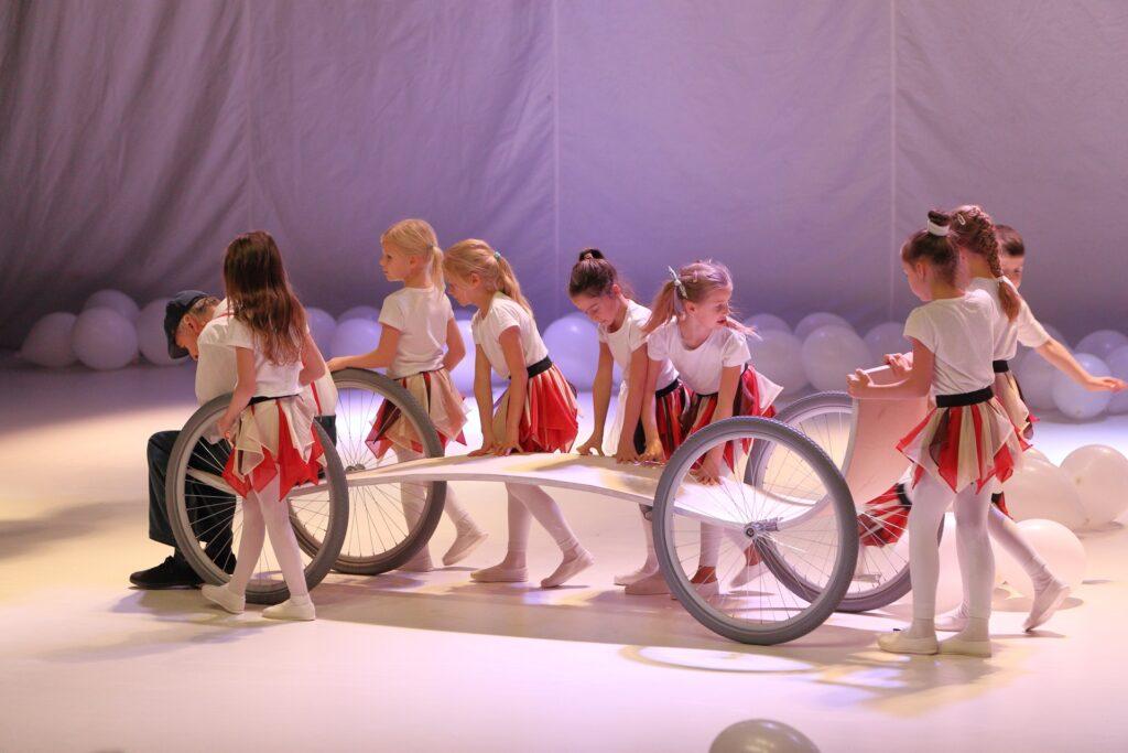 Na zdjęciu widzimy grupę dziewczynek. Jest ich osiem. Mają mniej więcej sześć, siedem lat. Ich uwaga w pełni skupiona jest na dziwnym pojeździe, wokół którego się zebrały. Jest to długa, fantazyjnie powyginana platforma na dużych, gumowanych kołach ze szprychami. Dziewczynki ubrane są jednakowo: w białe bluzeczki, rajstopy i tenisówki oraz krótkie, czerwono-żółte spódniczki z czarnym paskiem. Możemy domyślić się, że przed chwilą wspólnie pchały dziwny pojazd. Dwie, po lewej stronie fotografii, kontrolują jego przednie koła. Trzy pośrodku, pochylone, oparły dłonie na platformie. Pozostałe, ustawione z tyłu, gotowe są w każdej chwili do wprawienia pojazdu w ruch. W momencie wykonania fotografii nie jest to jednak możliwe. Na przedzie dziwnego wózka przysiadł bowiem starszy mężczyzna ubrany w białą koszulę, ciemne spodnie, czerwone szelki i ciemną czapkę z daszkiem. Mocno pochylił się do przodu i wygląda na zmęczonego. Jego stan zamyślenia kontrastuje z naturalną witalnością bijącą od dziewczynek. Cały obraz jest bardzo jasny. Dominuje na nim biały kolor podłogi, horyzontu i rozrzuconych w tle balonów.