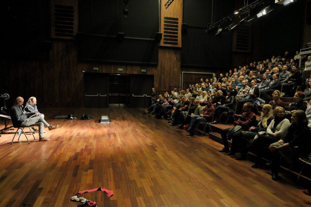 Zdjęcie wykonał fotograf stojący z boku, na linii styku sceny z widownią. Po prawej stronie pnie się w górę amfiteatralna widownia, szczelnie wypełniona siedzącymi na krzesłach widzami. Po lewej natomiast widnieje fragment sceny z porozrzucanymi rekwizytami, głównie sprzętem sportowym. Stoją tam też, w rozległej plamie jasnego światła, dwa krzesła, na których siedzą kobieta i mężczyzna. Postacie są niewielkie i trudno dostrzec szczegóły ich wyglądu.