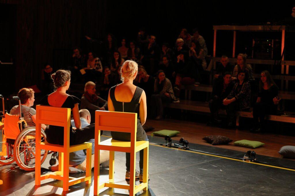 Fotografia wykonana została z głębi sceny, w kierunku widowni. Na pierwszym planie, w plamie jasnego światła po lewej stronie, siedzą artystki zwrócone plecami do obiektywu. Dwie z nich przycupnęły na dużych, masywnych żółtych krzesłach. Trzecia, najniższa, siedzi na wózku. U ich stóp na podłodze siedzi ze skrzyżowanymi nogami pochylony mężczyzna. Twarze aktorek zwrócone są w stronę siedzącej przodem do obiektywu publiczności. Sylwetki widzów są nieostre i wtapiają się w panujący w sali półmrok.