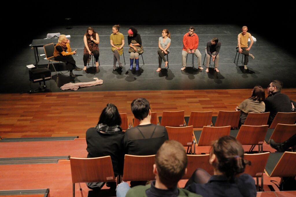 Na pustej scenie przykrytej czarną podłogą baletową siedzi osiem osób – pięć kobiet i trzech mężczyzn. Druga od lewej, aktorka, mówi do mikrofonu. Pozostali patrzą na nią, słuchając w skupieniu. Pierwszy plan zdjęcia wypełniają krzesła amfiteatralnej widowni oraz sylwetki uczestników spotkania siedzących na niektórych z nich.
