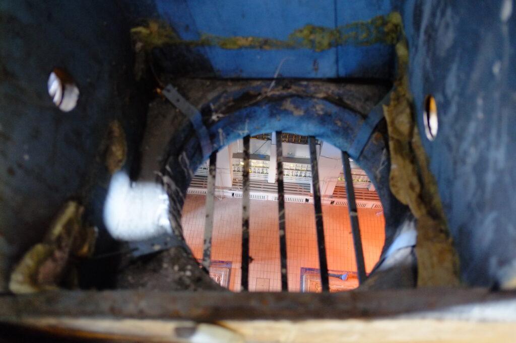 Fotografia przedstawia fragment synagogi przebudowanej na pływalnię. Wnętrze pokazane jest z perspektywy okrągłego otworu wentylacyjnego, zabezpieczonego metalowymi prętami. Obraz jest dość niewyraźny, ale można dostrzec pomarańczowe kafelki, które swoją barwę zawdzięczają zapewne wpadającemu światłu, oraz trudne do zidentyfikowania inne elementy wyposażenia basenu.