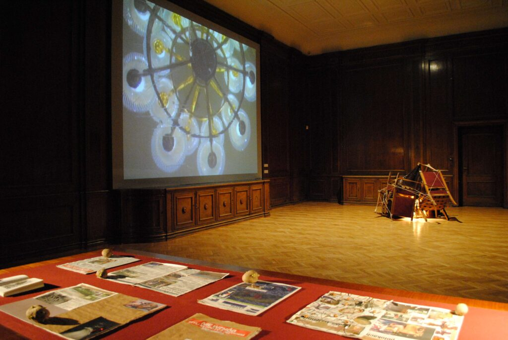 Fotografia przedstawia zamkowy Pokój Orzechowy, nazwa pokoju pochodzi od boazerii wykonanej z drewna orzechowego, pokrywającej wszystkie ściany pomieszczenia. Na pierwszym planie usytuowany jest blat starego drewnianego biurka, na którym leżą rozłożone popisane wycinki gazet, wykonane z nich kolaże oraz ziemniaki. W tle pomieszczenia stoi rzeźba zbudowana ze starych krzeseł poukładanych w stos i powiązanych sznurkami. Wewnątrz stosu ukryta jest świecąca lampka. Całość przywołuje skojarzenia z ogniskiem. Na ścianie po lewej stronie fotografii wyświetlany jest film ukazujący w ujęciu od dołu fragment zamkowego żyrandola. Motyw ten wygląda jak wielki abstrakcyjny obraz.