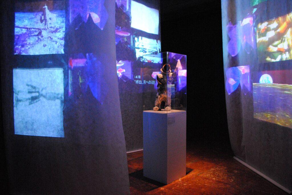Fotografia przedstawia zbliżenie instalacji artystycznej we wnętrzu Sali Kominkowej. Na pierwszym planie znajduje się biały postument, na którym ustawiona jest pod szklanym kloszem osobliwa rzeźba kosmonauty z głową ryby. Po bokach, pod różnym kątem zwieszają się delikatne tkaniny, na których wyświetlane są zdjęcia i filmy dokumentalne z podboju kosmosu. Przestrzeń na zdjęciu jest ciemna, a projekcje przywołują skojarzenia z centrum kontroli lotów kosmicznych.