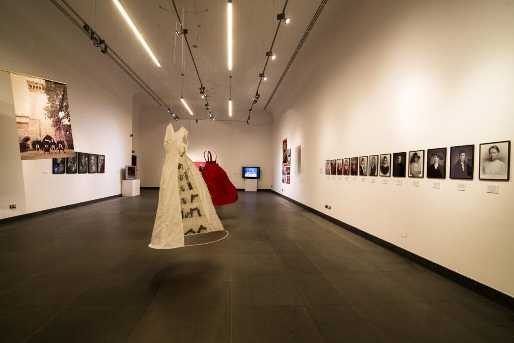 Na fotografii widzimy fragment aranżacji wystawy. Na białych ścianach, po prawej i lewej stronie znajdują się liczne fotografie, po środku, ponad grafitową podłogą, podwieszone są dwie rozkloszowane sukienki – biała i czerwona, z tyłu widać postawione na postumentach dwa telewizory. Całość oświetlana jest znajdującymi się pod sufitem szynami z lampami.