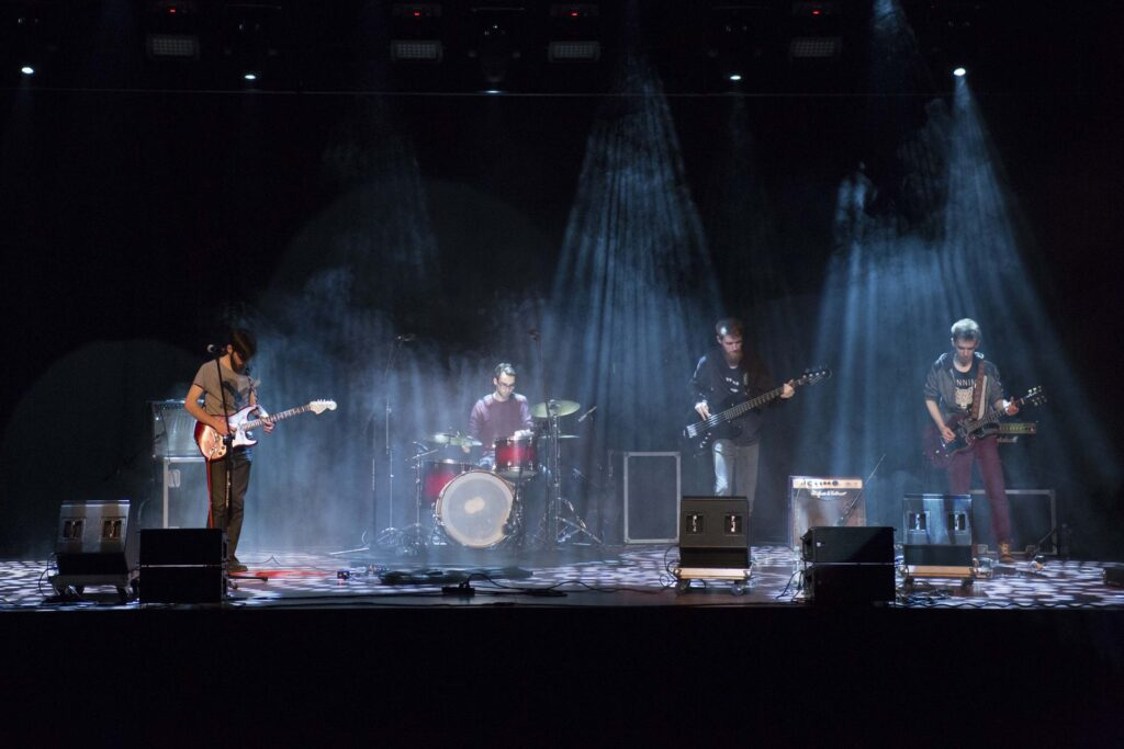 Zdjęcie z koncertu w ciemnej tonacji. Muzycy są oświetleni słabym białym światłem padającym na każdego z nich z góry. Na fotografii znajdują się (od lewej): basista, perkusista, basista i gitarzysta.