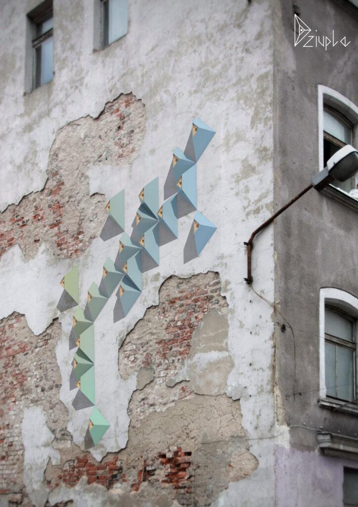 Na zdjęciu widać dwie narożne ściany starej kamienicy. Na elewacji z prawej strony znajdują się dwa okna, które w części środkowej przecina lampa na wysięgniku. Z lewej strony budynek jest mocno zniszczony, pozbawiony w dużej części tynku, z odsłoniętymi fragmentami muru ceglanego. W górnej części znajdują się dwa mniejsze okna, a w środkowej seledynowe i błękitne dziuple dla ptaków w kształcie czworościanów ze ściętymi czubkami.