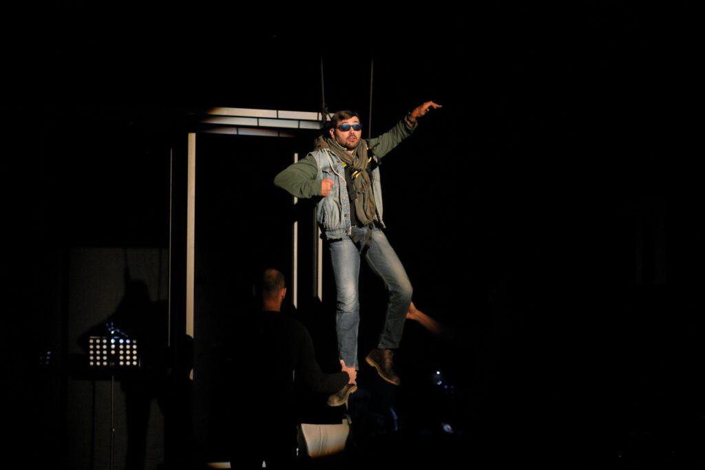 Zdjęcie przedstawia młodego mężczyznę biorącego udział w spektaklu. Podczas odgrywanej sceny, podwieszony na linach, unosi się nad podłogą. Ubrany jest w zieloną bluzę i dżinsową kamizelkę. Wokół szyi zawiązany ma sporych rozmiarów kolorowy szal, również w zielonej tonacji. Na nogach ma błękitne dżinsy i brązowe buty z żółtymi podeszwami. Znad ciemnych okularów rzucają się w oczy mocno zarysowane, uniesione brwi. Lewa ręka i noga sprawiają wrażenie, jakby maszerował w powietrzu. Za mężczyzną połyskują popielate fragmenty scenografii, a w dolnym lewym rogu oświetlony pulpit do nut. Tyłem do widzów usytuowana jest postać, która asekuruje aktora, delikatnie przytrzymując jego prawą nogę na wysokości kostki.
