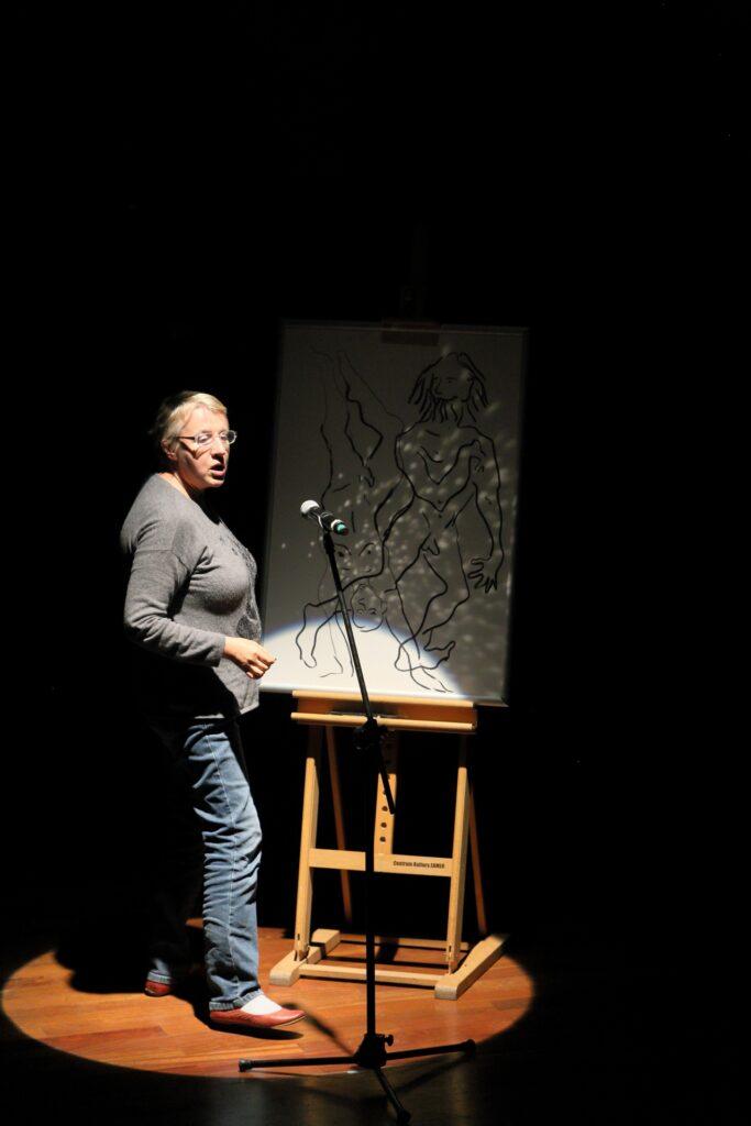 Zdjęcie przedstawia kobietę biorącą udział w spektaklu. Stoi bokiem, po lewej stronie. Ma siwe włosy i okulary. Ubrana jest w szarą bluzkę z długimi rękawami, niebieskie dżinsy i brązowe buty. W kręgu światła rzucanego przez reflektor oprócz postaci widzimy mikrofon umieszczony na czarnym statywie oraz dolną część malarskiej sztalugi. Umieszczony na niej w lekkim cieniu rysunek przedstawia dwie naszkicowane węglem sylwetki. Aktorka, mówiąc do mikrofonu, prawdopodobnie opowiada o pracy, którą przed chwilą stworzyła.